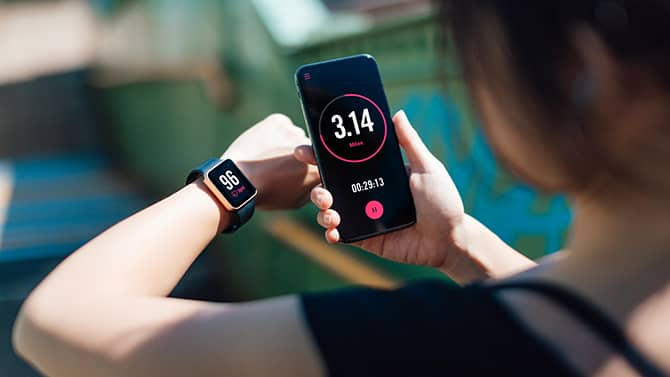 A woman using a fitness app on her smart phone and smart watch. Fitness tracking apps provide one example of the potential positive effects of technology on health.